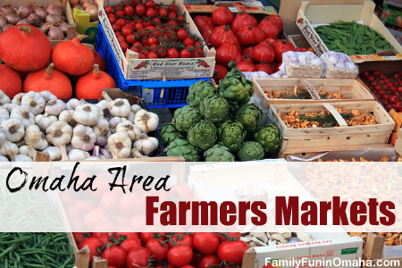 A variety of fresh fruit and vegetables on display at a farmers market with overlay text that reads Omaha Area Farmers Markets