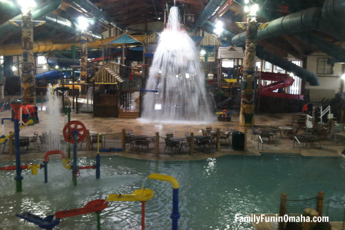 An indoor waterpark with splashing water from a bucket