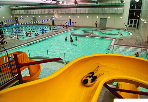 A person on a waterslide and an indoor pool at Omaha Kroc Center.