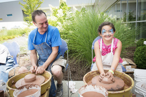 A man and a girl at pottery wheels at BaconFest Omaha.