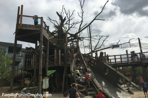 A group of people climbing a wooden structure at Children\'s Adventure Trails at the Omaha Zoo.