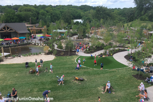 People in a grassy area at Children\'s Adventure Trails at the Omaha Zoo.