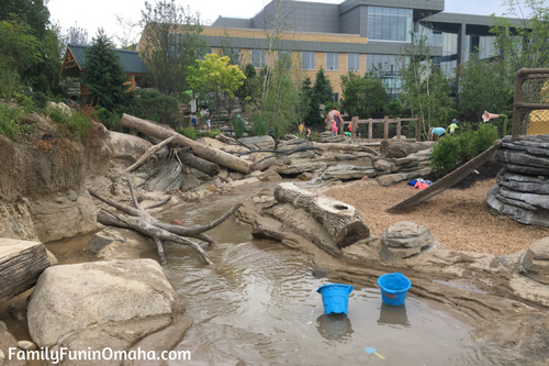 A stream in a water feature in front of a building at Children\'s Adventure Trails at the Omaha Zoo.