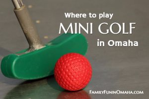 """A close up of a green golf putter and a red golf ball with overlay text that reads \""""Where to play mini golf in Omaha.\"""""""