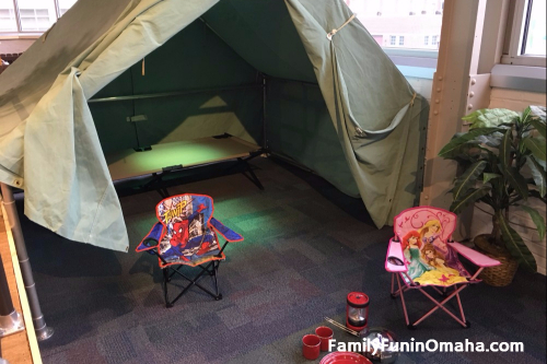 A close up of child-size camp chairs in front of a tent in Forever Forest at the Omaha Children\'s Museum.