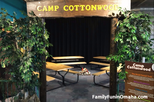 """An entrance sign in front of picnic tables that reads, \""""Camp Cottonwood\"""" at the Omaha Children\'s Museum."""