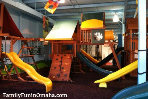 A large wooden playset inside of a building at Backyard Playworld.