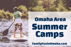 A young boy paddleboarding on a lake with overlay text that reads Omaha Area Summer Camps