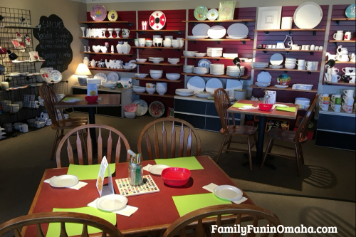 A dining room table in front of a pottery display at It\'s Yours Pottery.