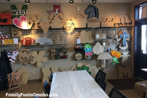 A table in front of a wall of unpainted wooden items at It\'s Yours Pottery.
