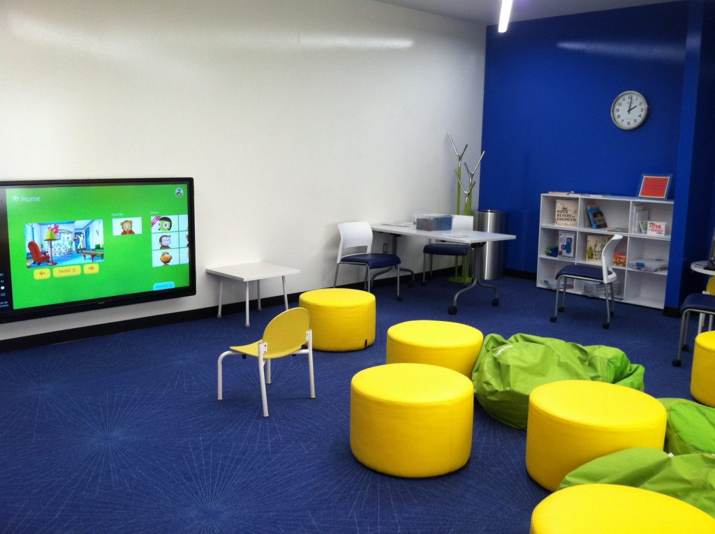 An indoor children\'s play area with books, tv, and comfortable seating