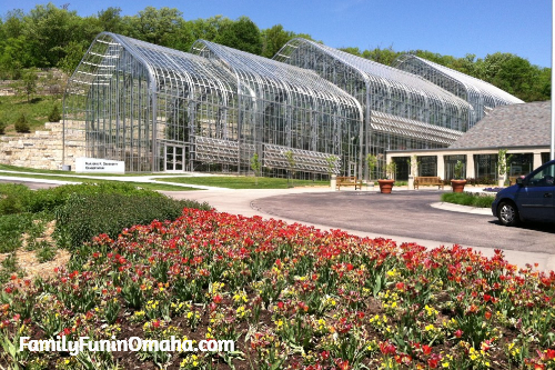 A close up of a flower garden in front of a glass building at Lauritzen Gardens