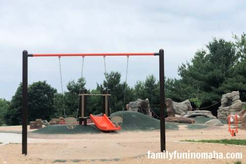 Swings with a slide in the background at Standing Bear Lake Playground.
