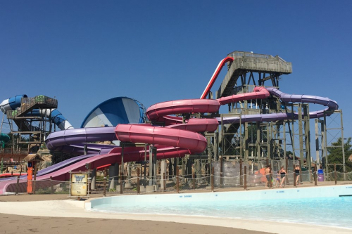 An outdoor waterpark slide by a shallow pool