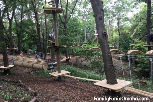 A person standing on a wooden platform at Tree Rush Adventures.