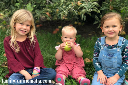 Three little girls sitting in front of a tree at Arbor Day Farm.