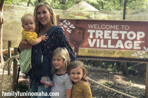 A family posing for a picture in front of the welcome sign at Arbor Day Farm.