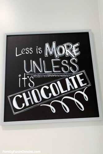 """A sign that reads \""""Less is More Unless it\'s chocolate\"""" at Baker\'s Candies."""