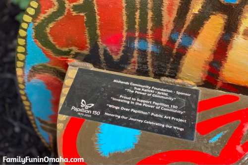 A close up of a sign on a large colorful butterfly bench in Papillion.